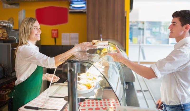 Kvinnlign shoppar ägareportionsmörgåsen till den manliga kunden arkivbilder