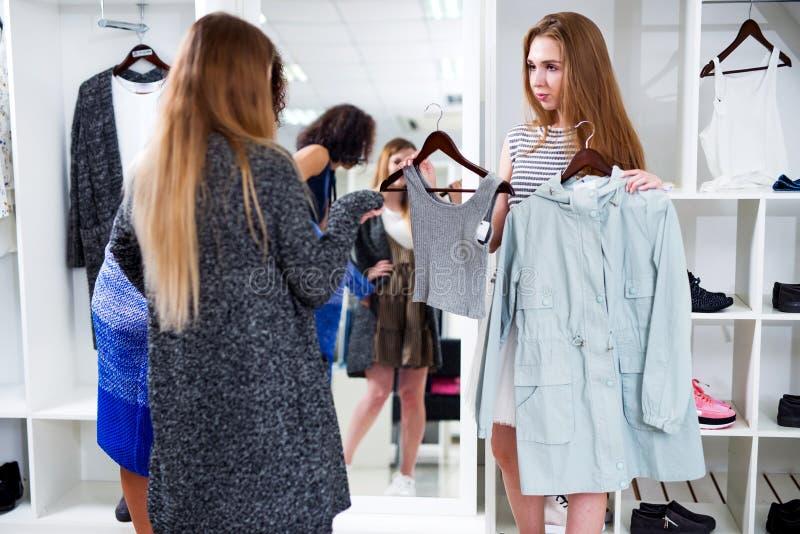 Kvinnlign shoppar assistenten som erbjuder två objekt av kläder till kunderna i modelager arkivfoto