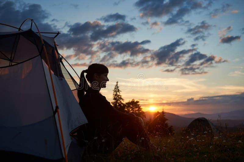 Kvinnlign sitter i tält överst av berget som tycker om solnedgången på suddiga bakgrundskullar royaltyfri foto