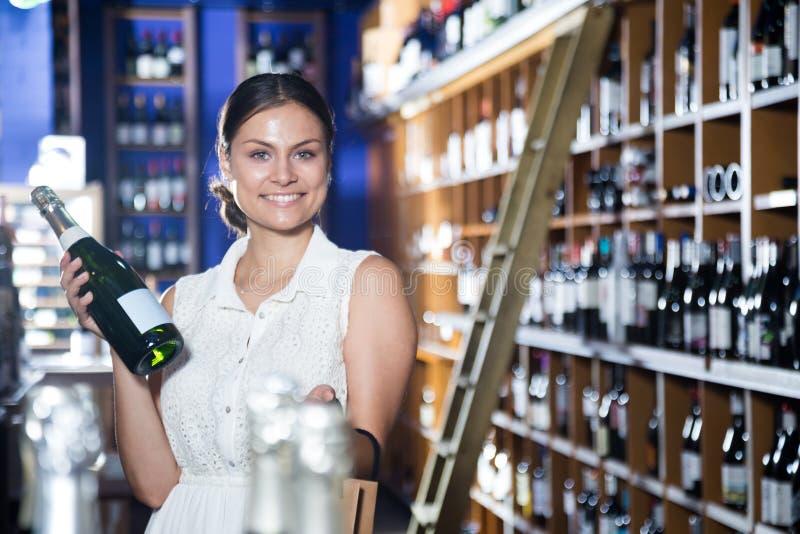 Kvinnlign ska erbjuda vin inom lagret royaltyfria foton