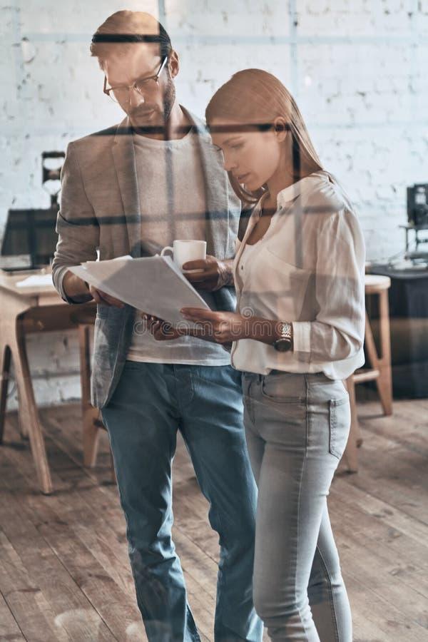 kvinnlign som manlign models en, sköt tillsammans två som fungerar Två affärskollegor som arbetar med dokument arkivbild