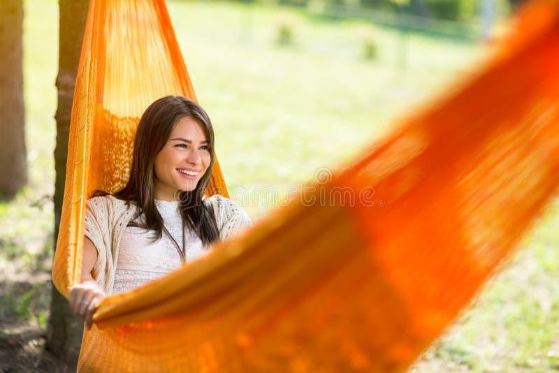 Kvinnlign som ner ligger i hängmatta och, vilar royaltyfria foton