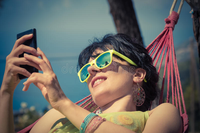 Kvinnlign tycker om på hängmattan och att använda den smarta telefonen arkivbild