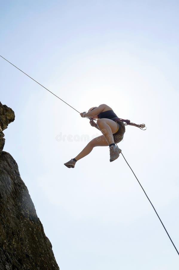 Kvinnlign vaggar klättraren som Rappelling arkivbild