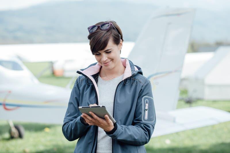 Kvinnligpilot som använder en minnestavla royaltyfri foto