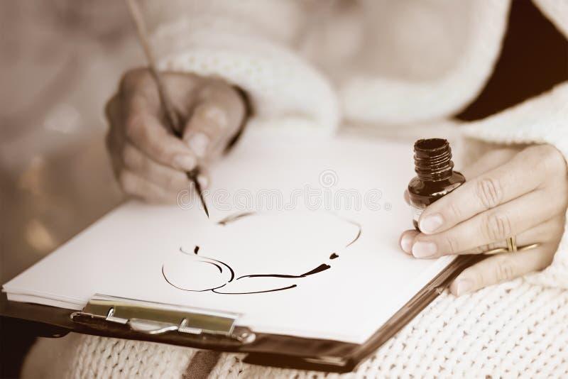 Kvinnligs händer som drar en karikatyr med svart färgpulver arkivfoton