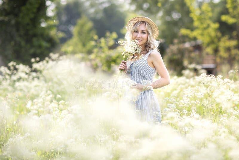 Kvinnligst?ende utomhus en kvinna i en sugr?rhatt i ett blommaf?lt med en bukett av l?sa blommor royaltyfria bilder