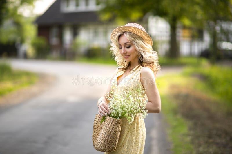 Kvinnligst?ende utomhus en kvinna i en sugr?rhatt i ett blommaf?lt med en bukett av l?sa blommor Sommar i landet royaltyfria bilder