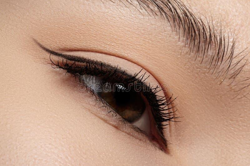 Kvinnligt öga för härlig closeup med smink för modesvarteyeliner royaltyfria bilder