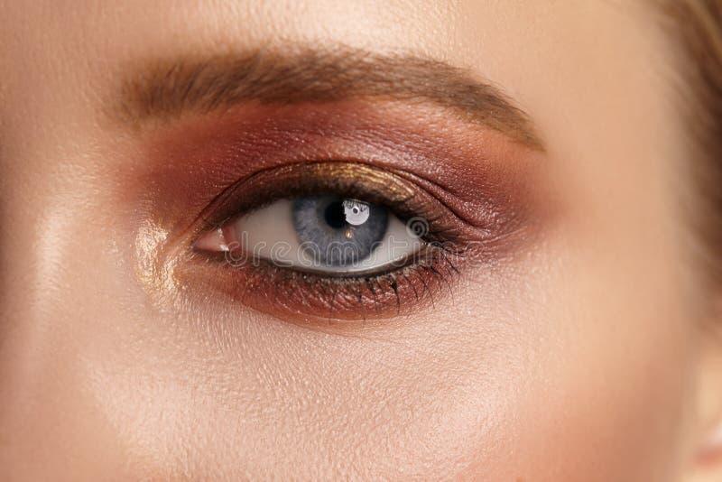 Kvinnligt öga för närbild med ljus röd makeup fotografering för bildbyråer