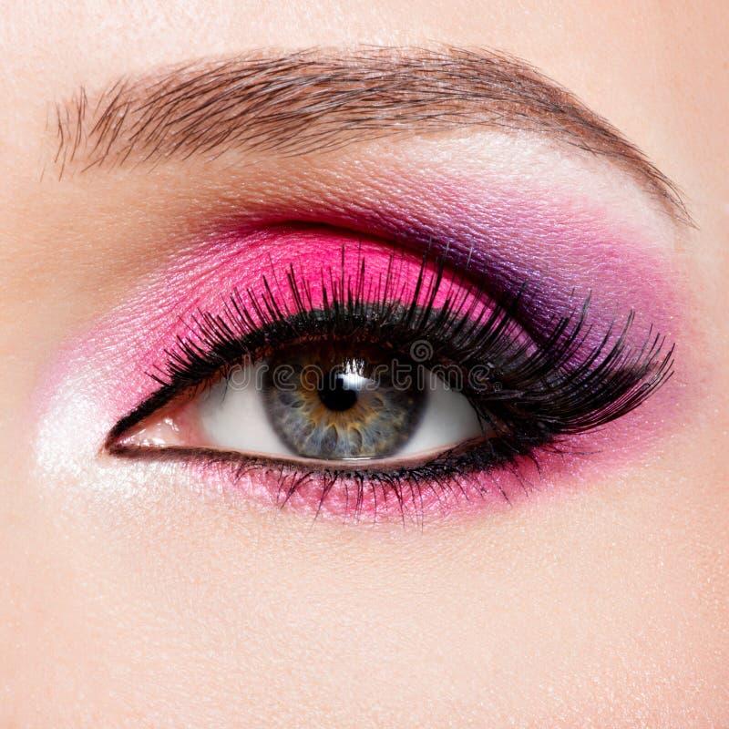 Kvinnligt öga med ljus rosa makeup för härligt mode royaltyfria bilder