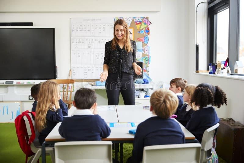Kvinnligt anseende för skolalärare i ett klassrum som gör en gest till skolbarn som sitter på en tabell som lyssnar arkivfoto