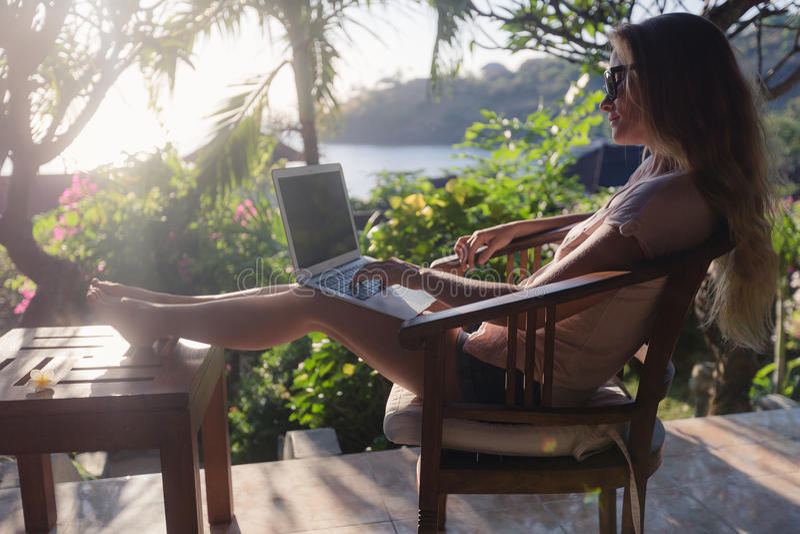Kvinnligt arbete med hennes bärbar dator utomhus royaltyfri fotografi