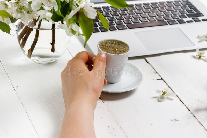 Kvinnligt arbetsplatsbegrepp Bekv?m kvinnlighetworkspace f?r frilans- mode med b?rbara datorn, kaffe, blommor p? vit bakgrund arkivfoton
