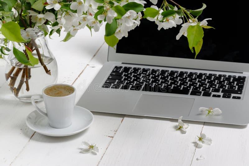 Kvinnligt arbetsplatsbegrepp Bekv?m kvinnlighetworkspace f?r frilans- mode med b?rbara datorn, kaffe, blommor p? vit bakgrund royaltyfri fotografi