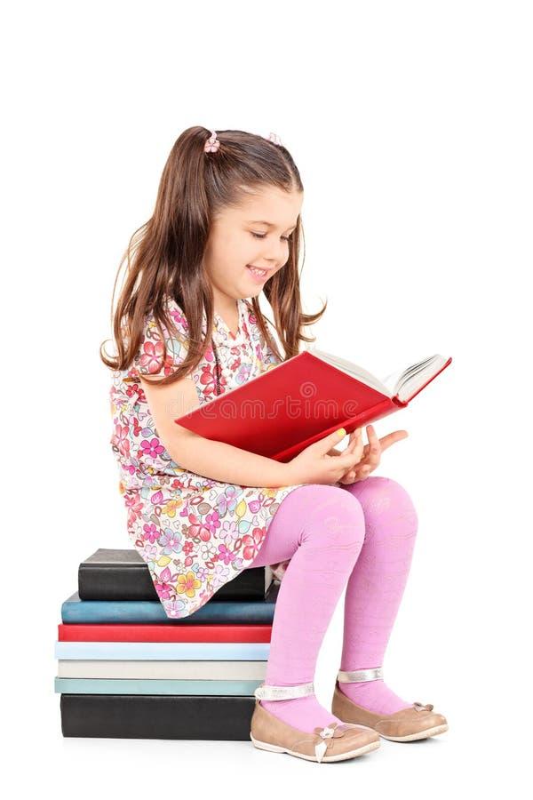 Kvinnligt barn som läser en placerad berättelse på bunt av böcker arkivbilder
