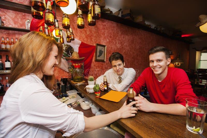Kvinnligt bartenderportionöl till män på stångräknaren arkivbilder