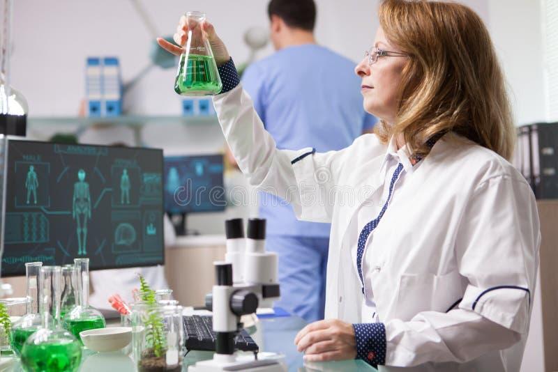 Kvinnligt biologinnehav och analysering av en lösning för sunda grönsaker royaltyfria foton