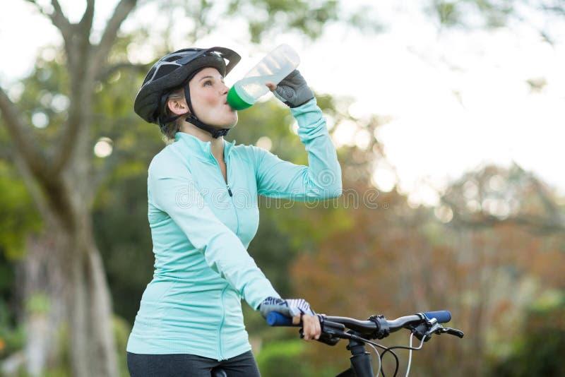 Kvinnligt cyklistdricksvatten i skog royaltyfria foton