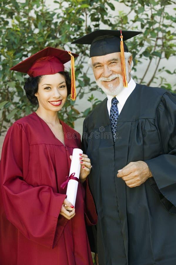 Kvinnligt doktorand- hållande certifikat med dekan royaltyfria foton