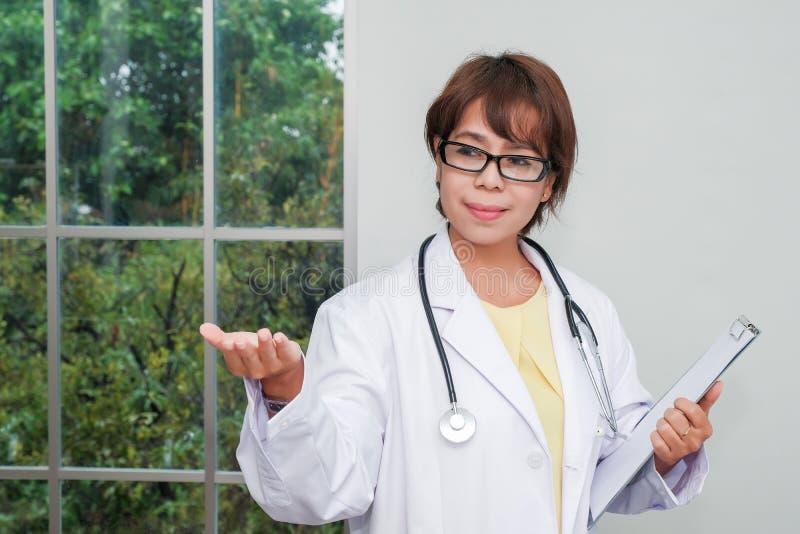Kvinnligt doktorsanseende för brunett med skrivplattan nära fönster royaltyfri bild