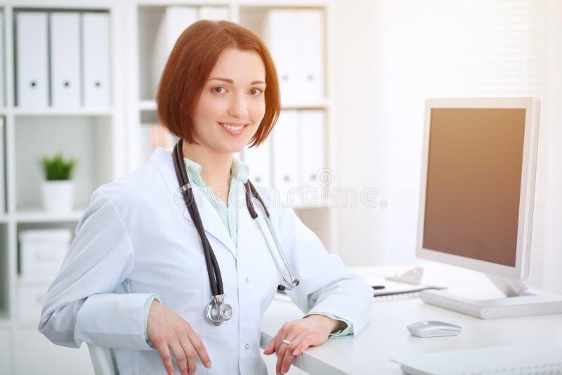 Kvinnligt doktorssammanträde för ung brunett på tabellen och arbete med datoren på sjukhuskontoret royaltyfria foton