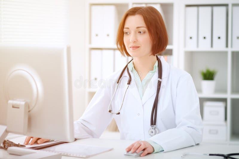 Kvinnligt doktorssammanträde för ung brunett på tabellen och arbete med datoren på sjukhuskontoret royaltyfri bild