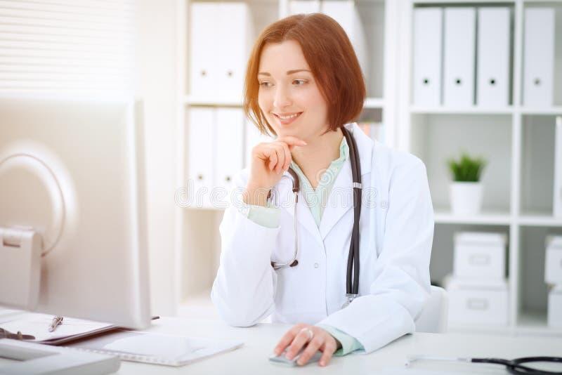 Kvinnligt doktorssammanträde för ung brunett på tabellen och arbete med datoren på sjukhuskontoret royaltyfri foto