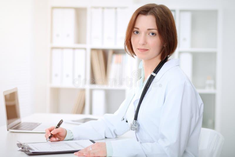 Kvinnligt doktorssammanträde för ung brunett på tabellen och arbete på sjukhuskontoret royaltyfri fotografi
