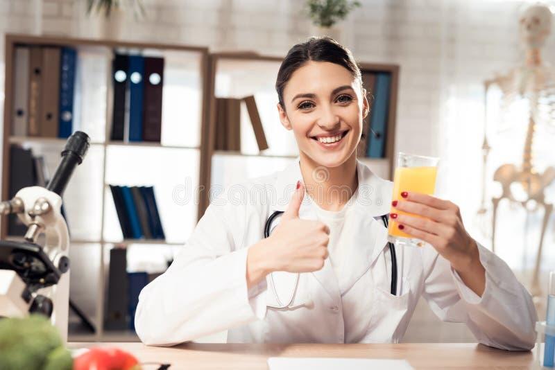Kvinnligt doktorssammanträde på skrivbordet i regeringsställning med mikroskopet och stetoskopet Kvinnan är hållande fruktsaft arkivfoto