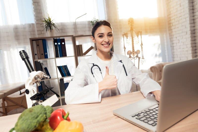 Kvinnligt doktorssammanträde på skrivbordet i regeringsställning med mikroskopet och stetoskopet Kvinnan ger upp tummar royaltyfri fotografi