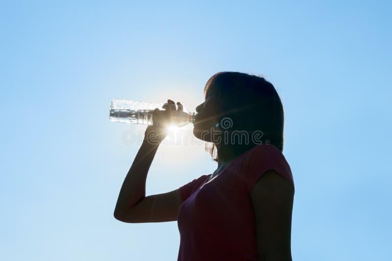Kvinnligt dricksvatten i varm sommar - begrepp för värmeslaglängd royaltyfri fotografi