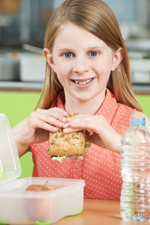 Kvinnligt elevsammanträde på tabellen, i att äta för skolakafeteria som är sunt royaltyfria bilder