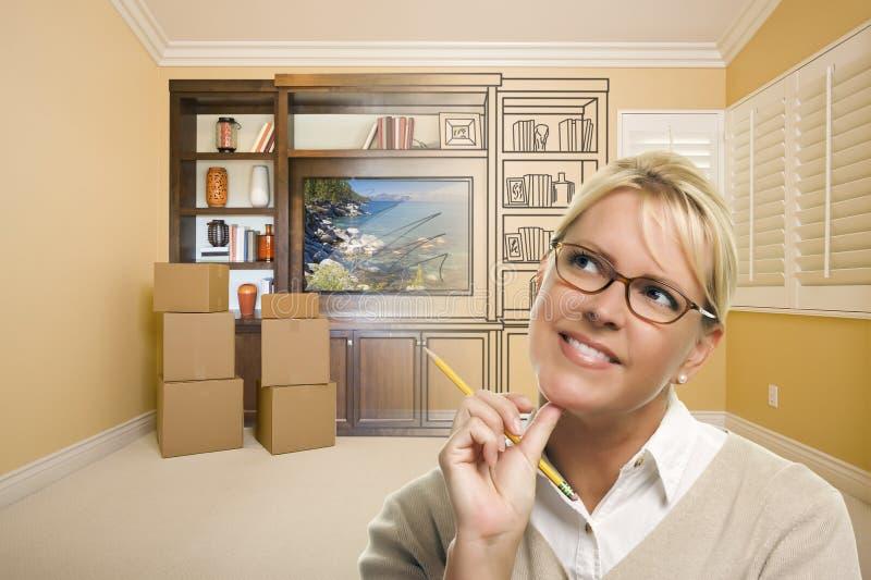 Kvinnligt formgivareHolding Pencil In rum med teckningen av underhållningenheten arkivbild