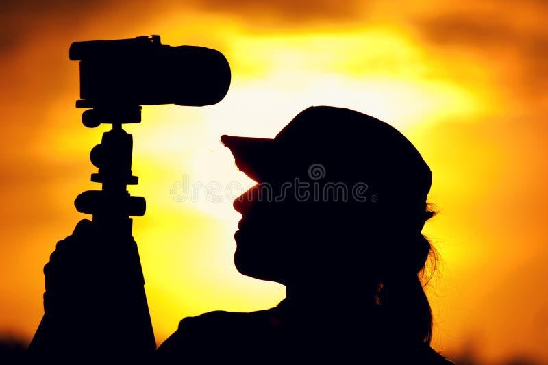 Kvinnligt fotografanseende mot inställningssolen royaltyfri fotografi