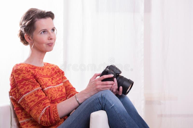 Kvinnligt fotografsammanträde i fåtölj fotografering för bildbyråer