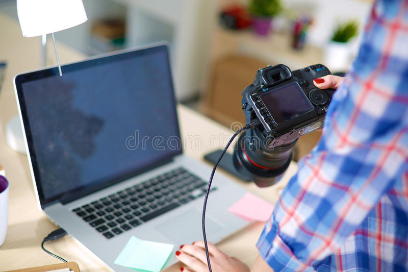 Kvinnligt fotografsammanträde på skrivbordet med royaltyfri bild