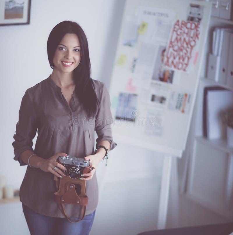 Kvinnligt fotografsammanträde på skrivbordet med bärbara datorn arkivbilder