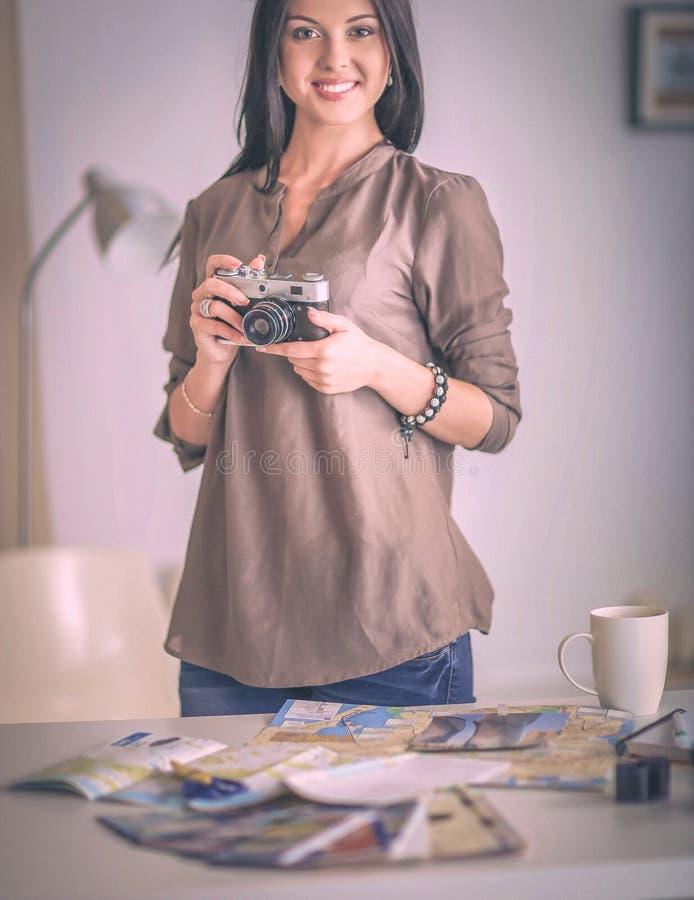 Kvinnligt fotografsammanträde på skrivbordet med bärbara datorn arkivbild
