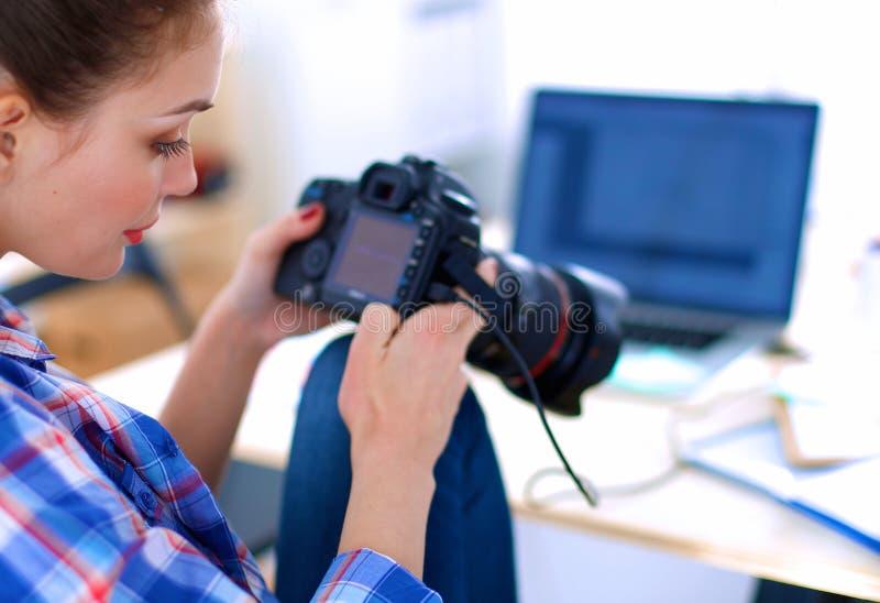 Kvinnligt fotografsammanträde på skrivbordet med bärbara datorn arkivfoton