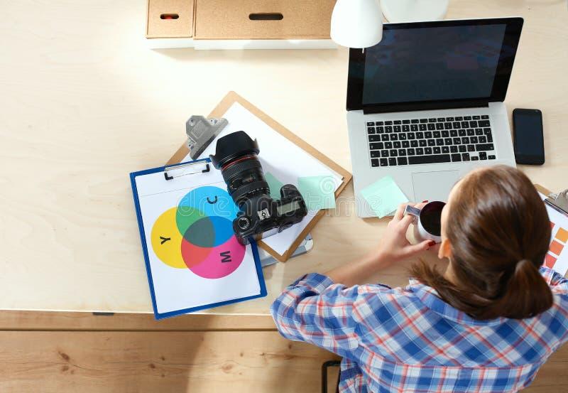 Kvinnligt fotografsammanträde på skrivbordet med bärbara datorn royaltyfria bilder