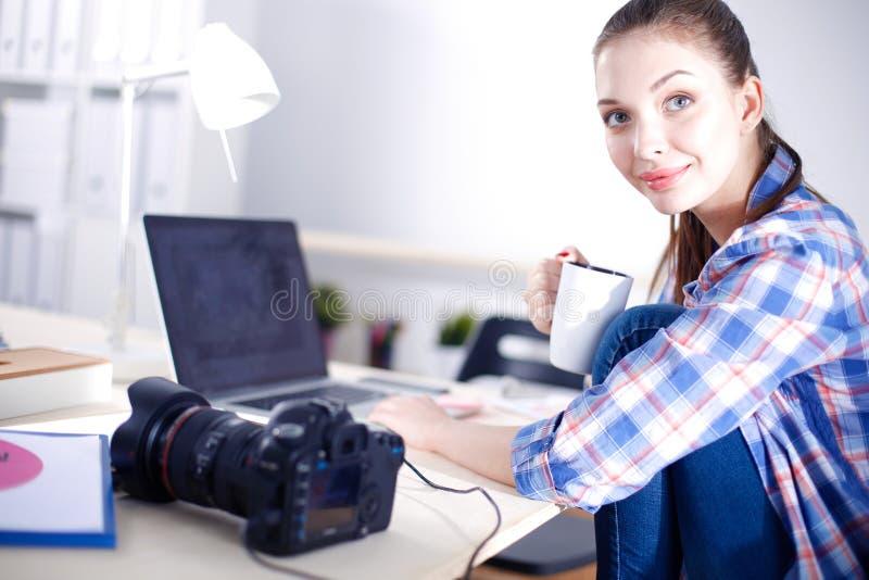 Kvinnligt fotografsammanträde på skrivbordet med bärbara datorn Kvinnlig fotograf arkivfoto