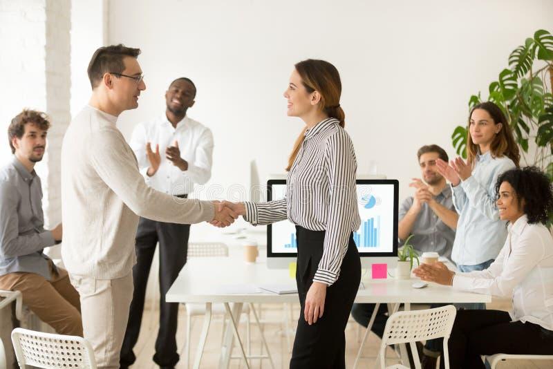 Kvinnligt framstickande som främjar manlig anställd för lönande handshaking medan arkivbild