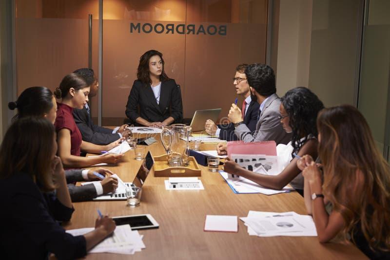 Kvinnligt framstickande som presiderar ett affärsmöte i en styrelse royaltyfri bild