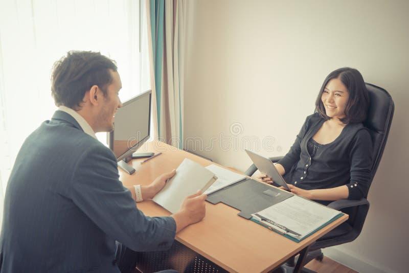 Kvinnligt framstickande som skrattar, medan intervjua det manliga sökandet arkivbilder