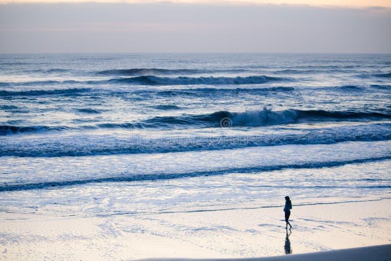Kvinnligt gå på kusten av ett hav med att förbluffa vågor och molnig himmel fotografering för bildbyråer