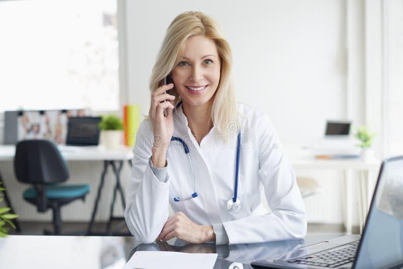 Kvinnligt ge sig för doktor råder på telefonen arkivfoto