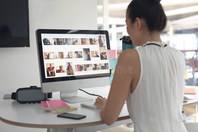 Kvinnligt grafiskt märkes- dricksvatten, medan arbeta på datoren på skrivbordet i ett modernt kontor arkivbild