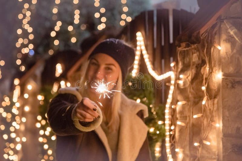 Kvinnligt hållande tomtebloss mot dekorerat hus för julljus royaltyfri foto