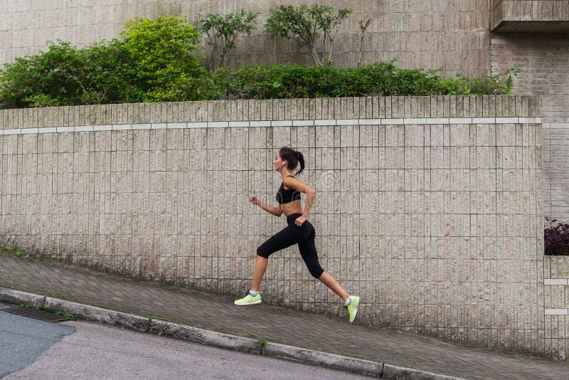 Kvinnligt köra för löpare som är stigande på stadgatan Sportig ung kvinna som utomhus gör cardio övningar fotografering för bildbyråer